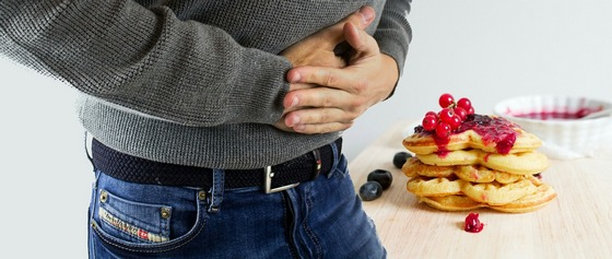 Man holding his stomach, having food-caused stomach upset