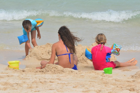 Children having fun on beach with their mom