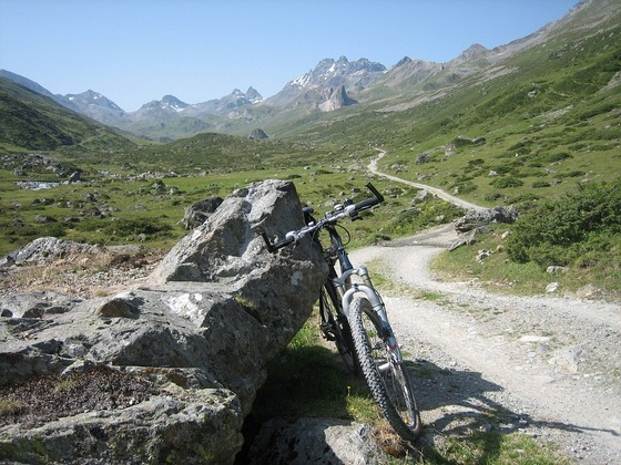 A bicycle leaning against a rock on a mountain trek