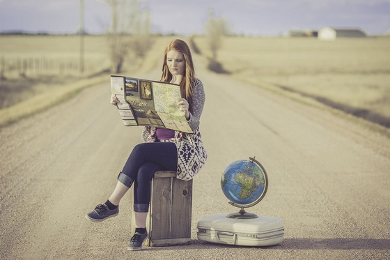 A lone woman sitting on a road, reading a map, with a suitcase and a globe.