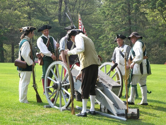 Men dressed in old-fashioned soldier uniforms gather around a cannon.