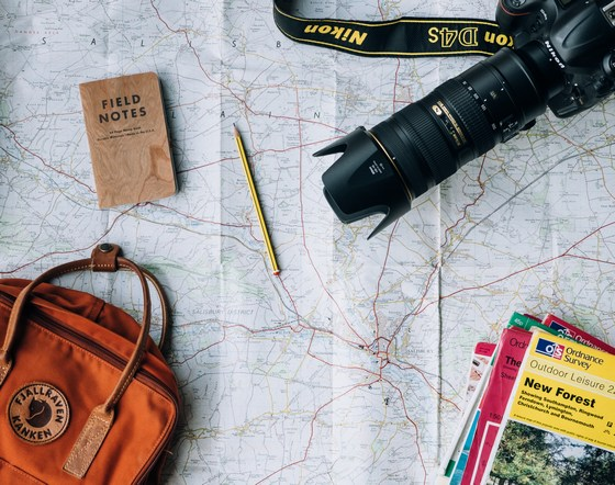 Map with travel brochures, camera, notebook and a travel bag