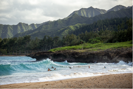Swimmers in waves on a bay beach in Hawaii