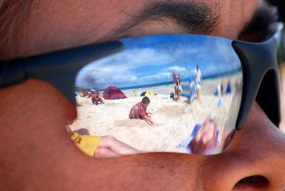 Beach scene reflection in sunglasses worn by a man